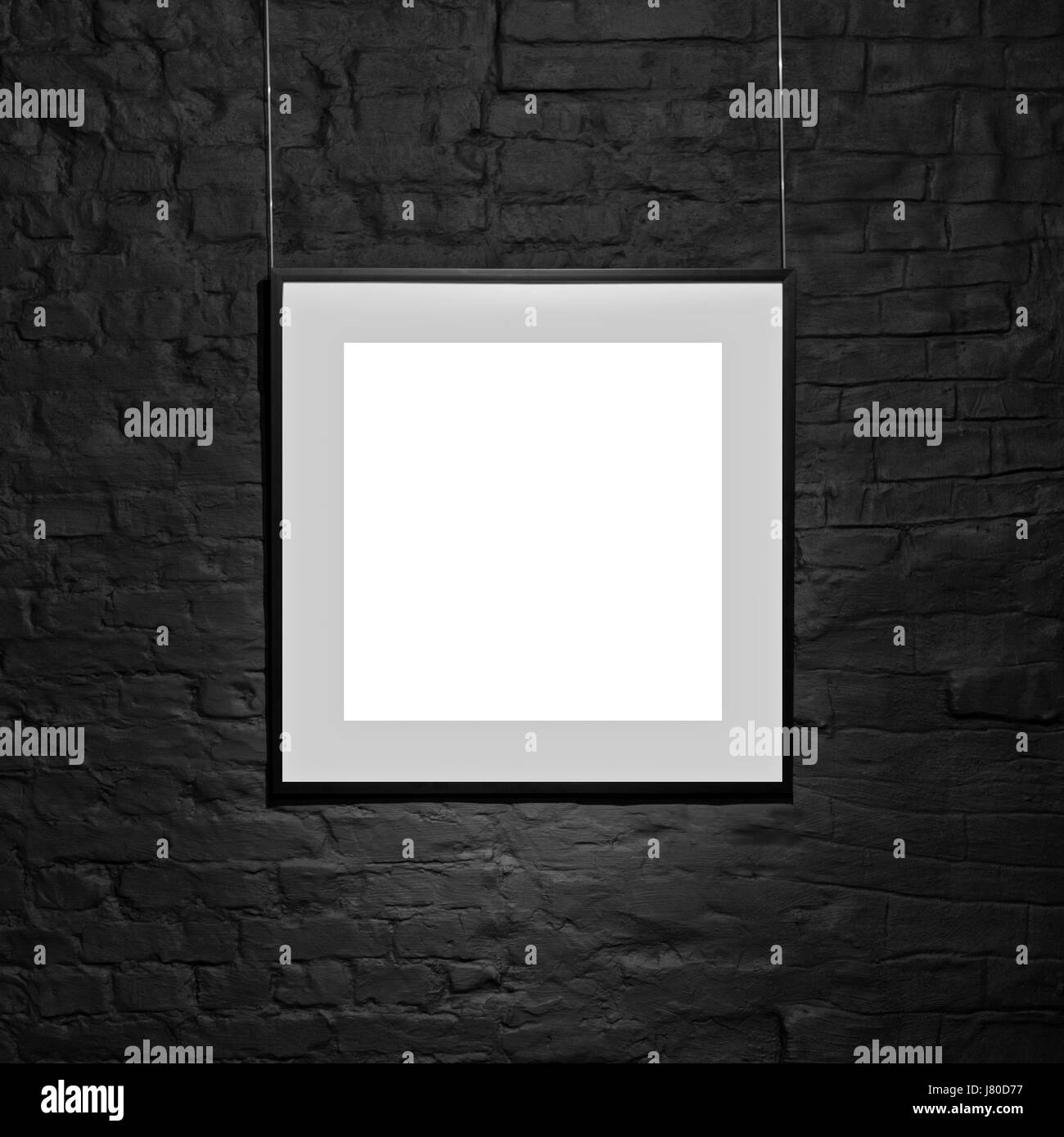 Leeren quadratischen Rahmen auf schwarze Mauer. Leerstelle Poster ...