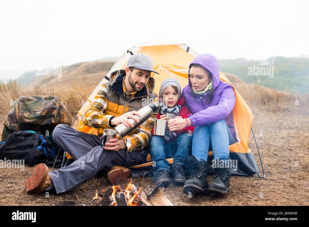 Familie mit einem Kind in der Nähe von Zelt sitzen und trinken heißen Tee aus der Thermoskanne beim Ausruhen in Stockfoto