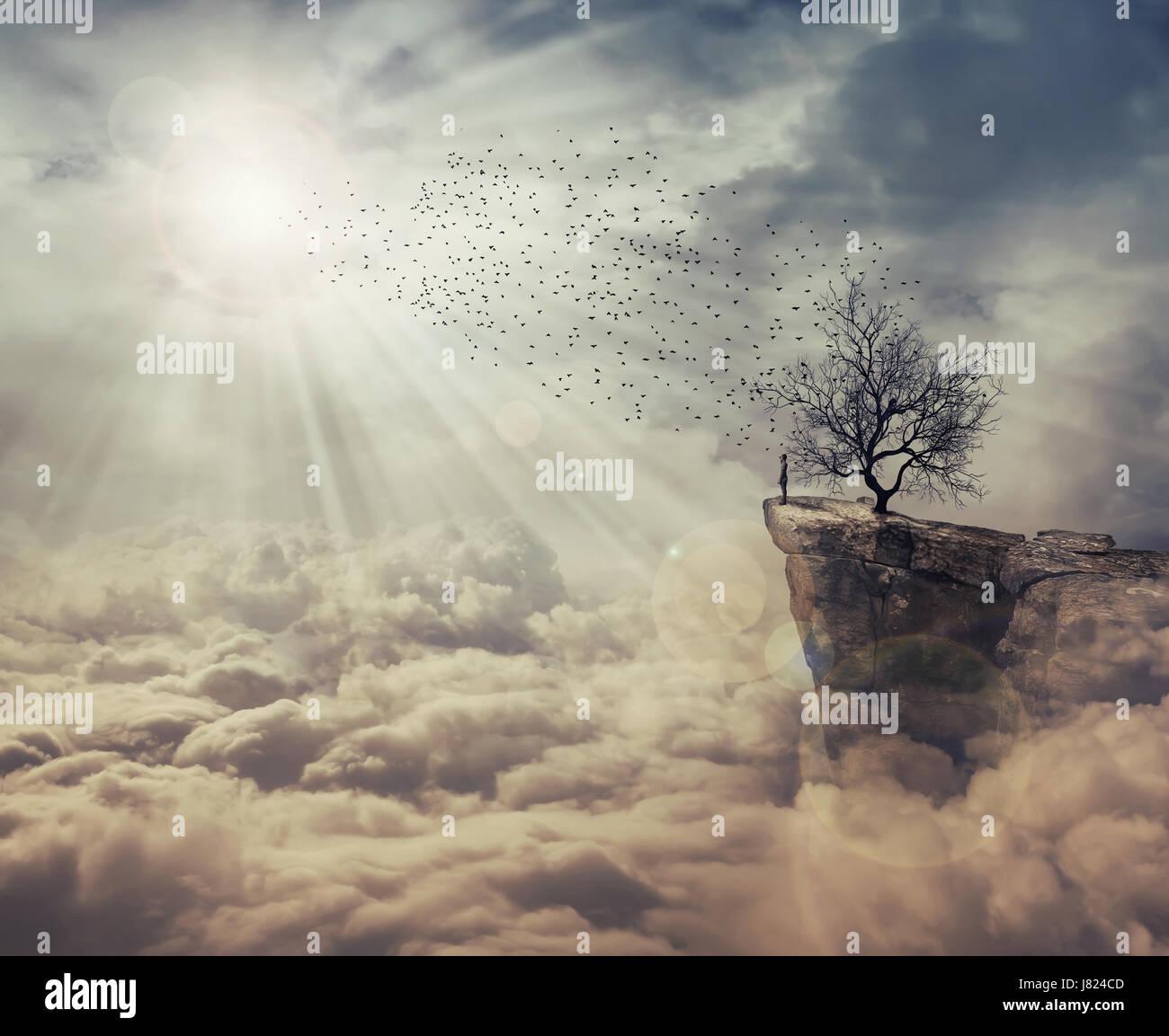 Junger Mann stand an der Spitze einer Klippe über den Wolken in einen Vogelschwarm fliegt von einem seltsam, Stockbild
