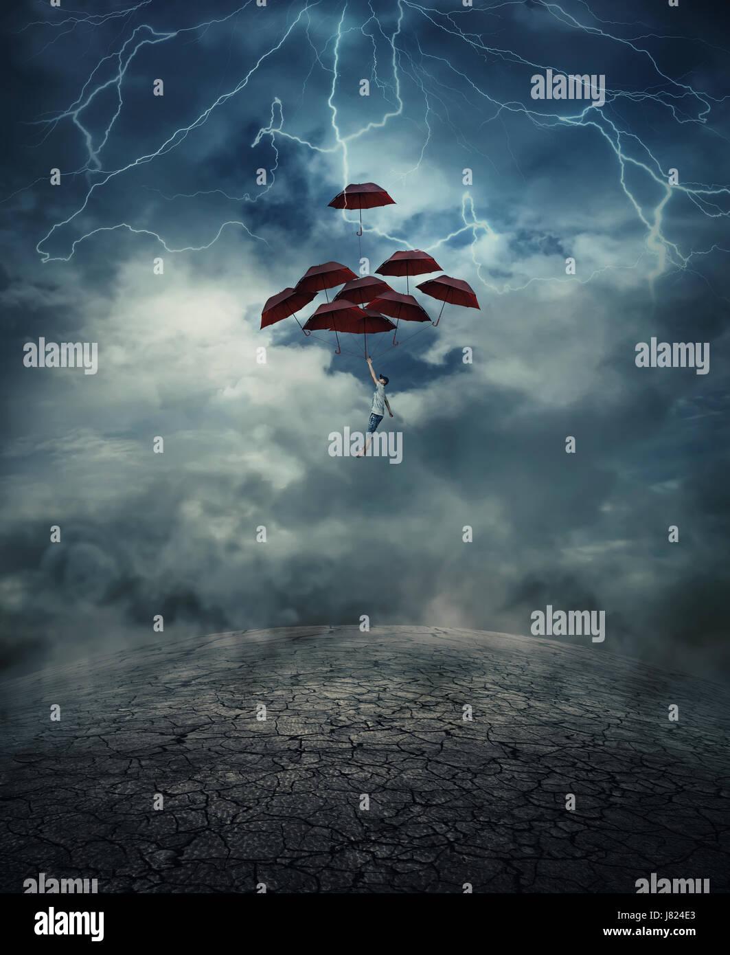 Junger Mann mit einer Menge von Regenschirmen als eine Luftballon steigen bis in den Himmel voller Blitze über Stockbild