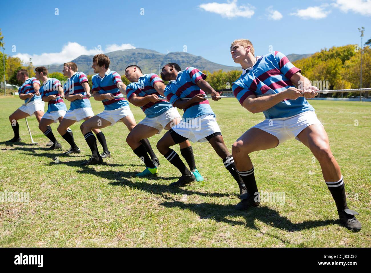 Volle Länge des Rugby-Spieler spielen Tauziehen auf Wiese gegen Himmel Stockbild
