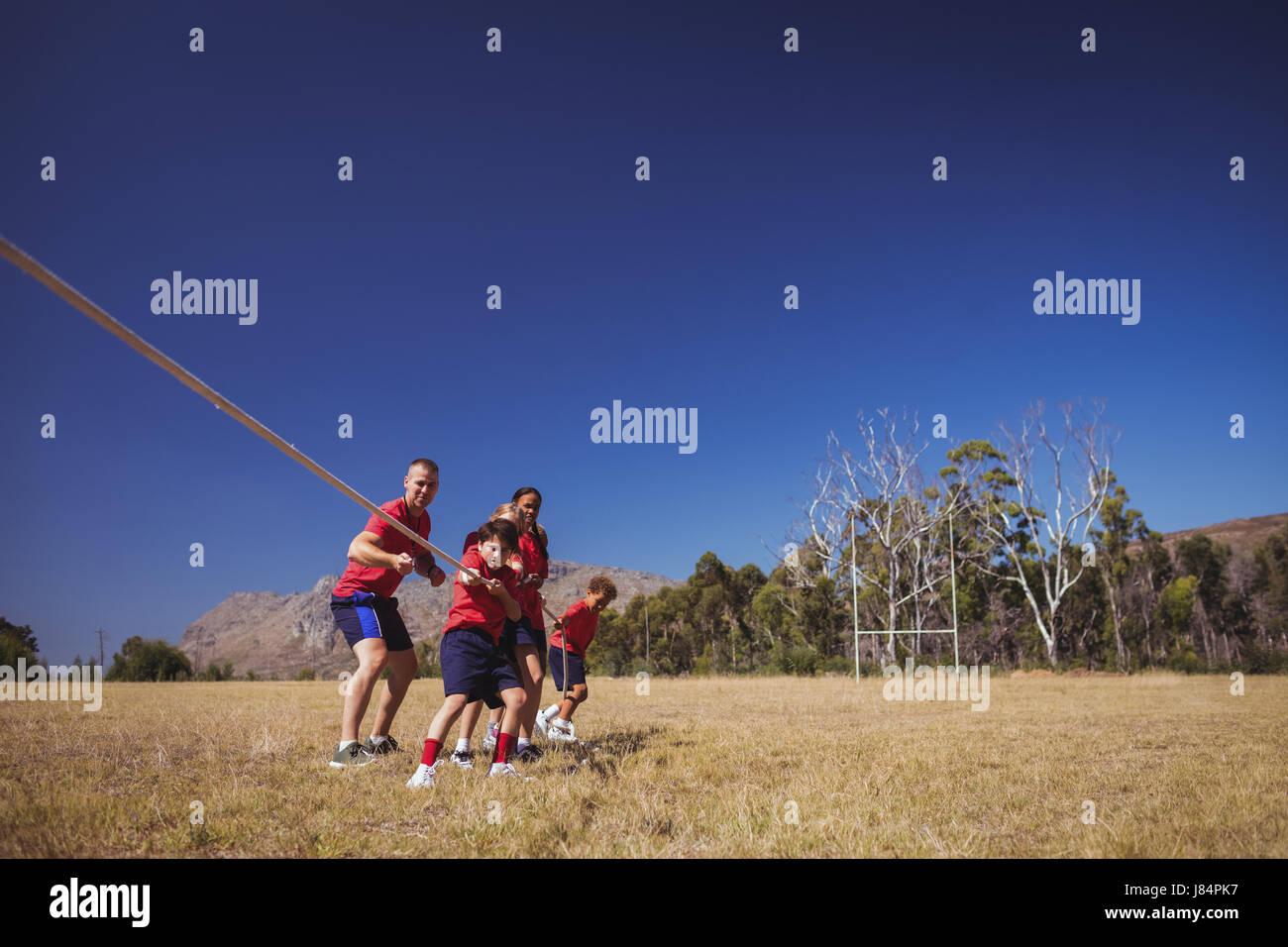 Trainer unterstützen Kinder im Tauziehen beim Hindernis-Parcours-Training im Boot camp Stockbild