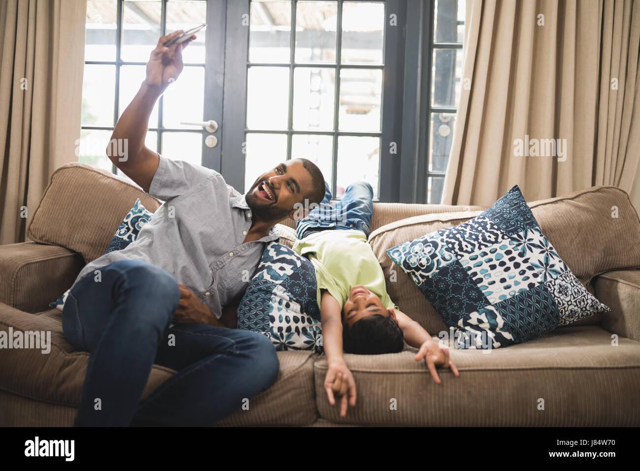 Fröhlicher Mensch unter Selfie mit seinem Sohn auf Couch zu Hause Stockfoto