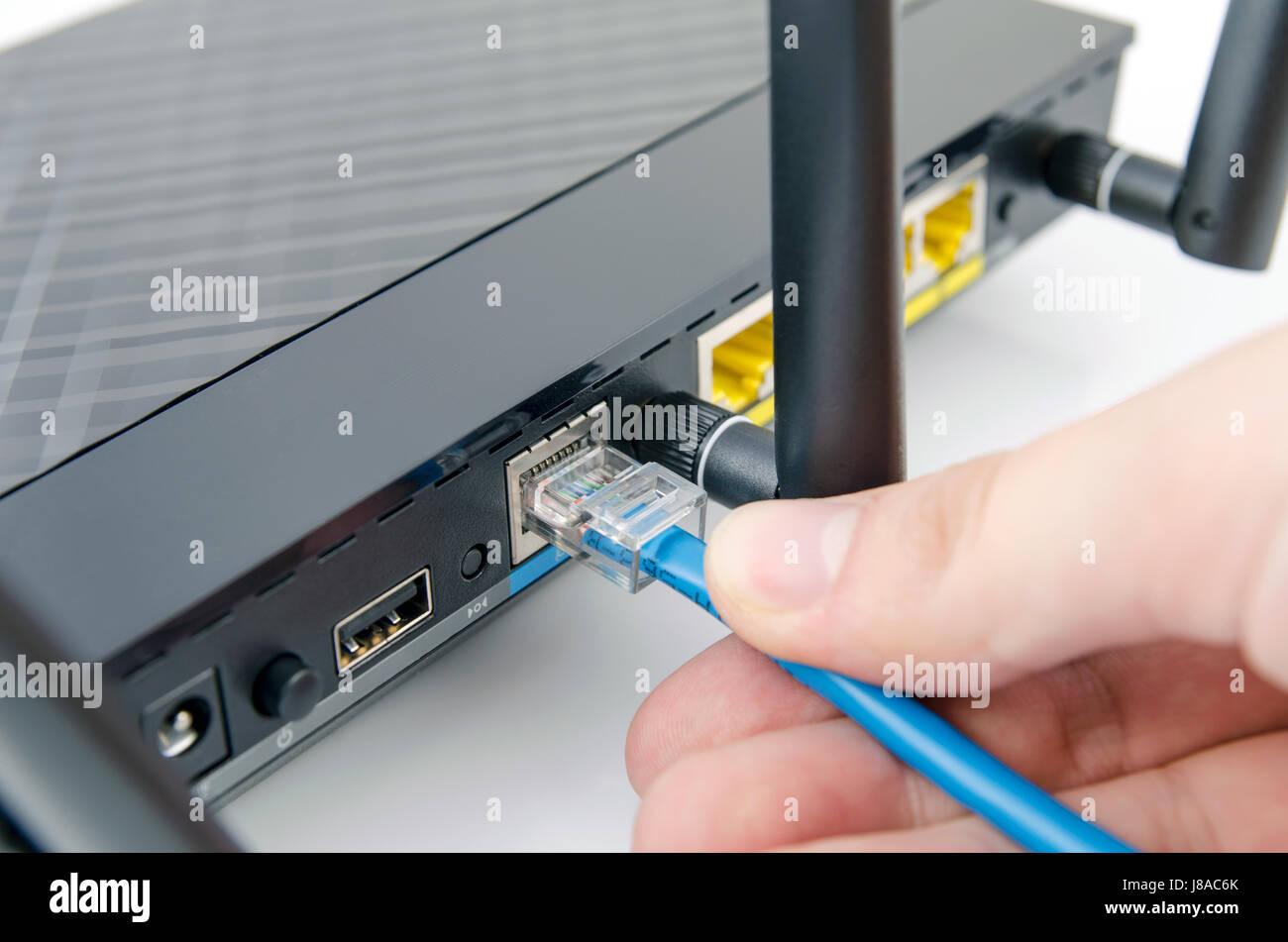 mann lässt sich internet-kabel an den router. router wlan-ethernet