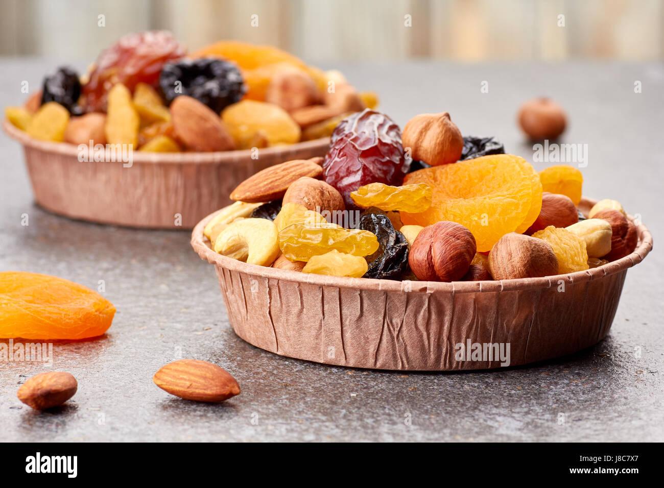Papierformulare mit Mischung aus Trockenfrüchten und Nüssen über Stein Hintergrund Stockbild