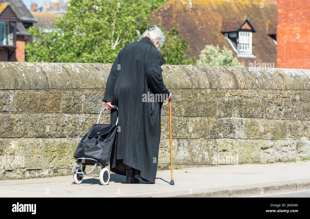 Ältere Frau gekleidet in schwarz mit einem Wagen und zu Fuß über eine alte Steinbrücke Spazierstock. Stockbild