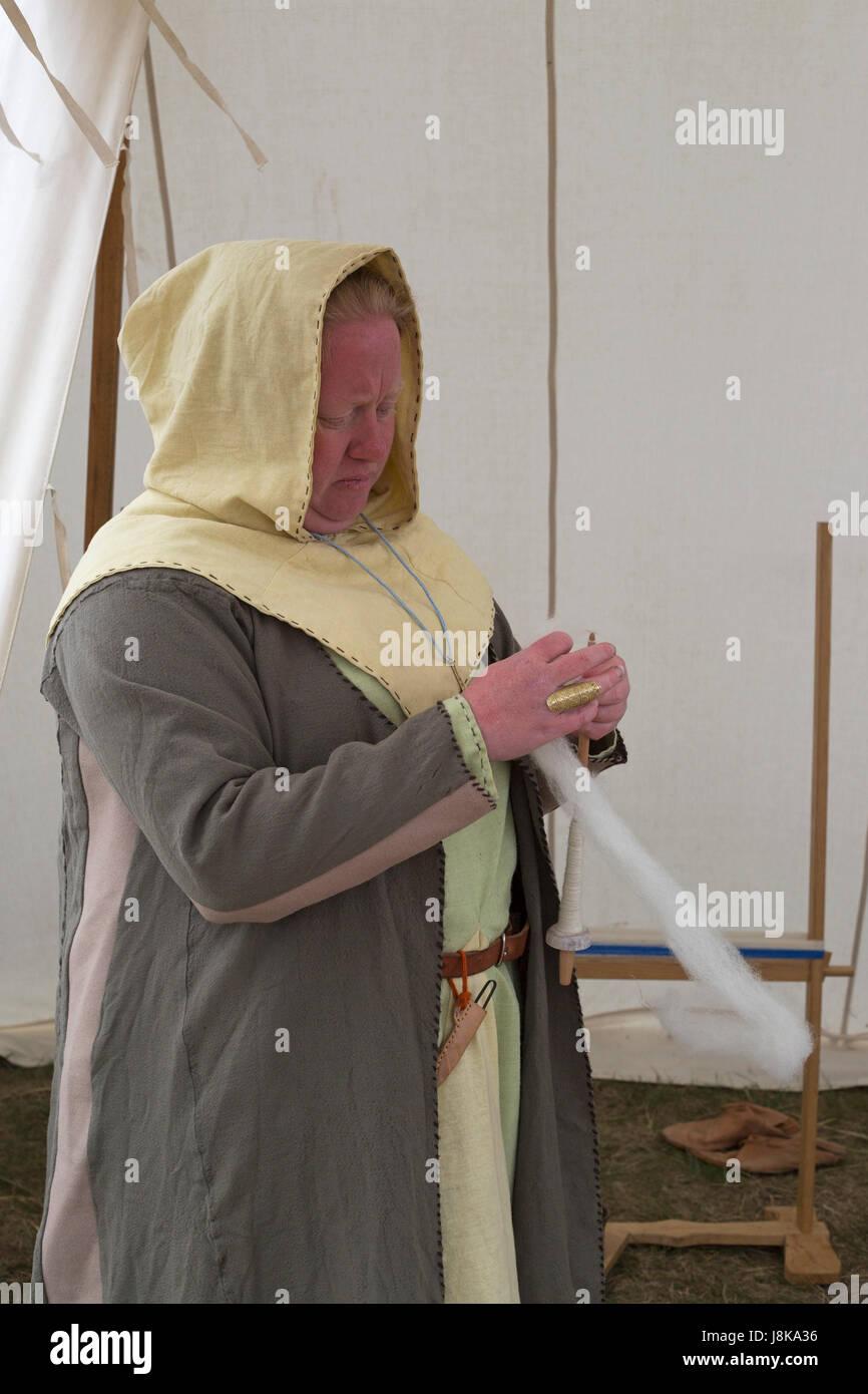 Gekleidete Frau im traditionellen Kostüm Spinnen Wolle im Zelt am Nachbau des Wikinger-Siedlung Stockbild