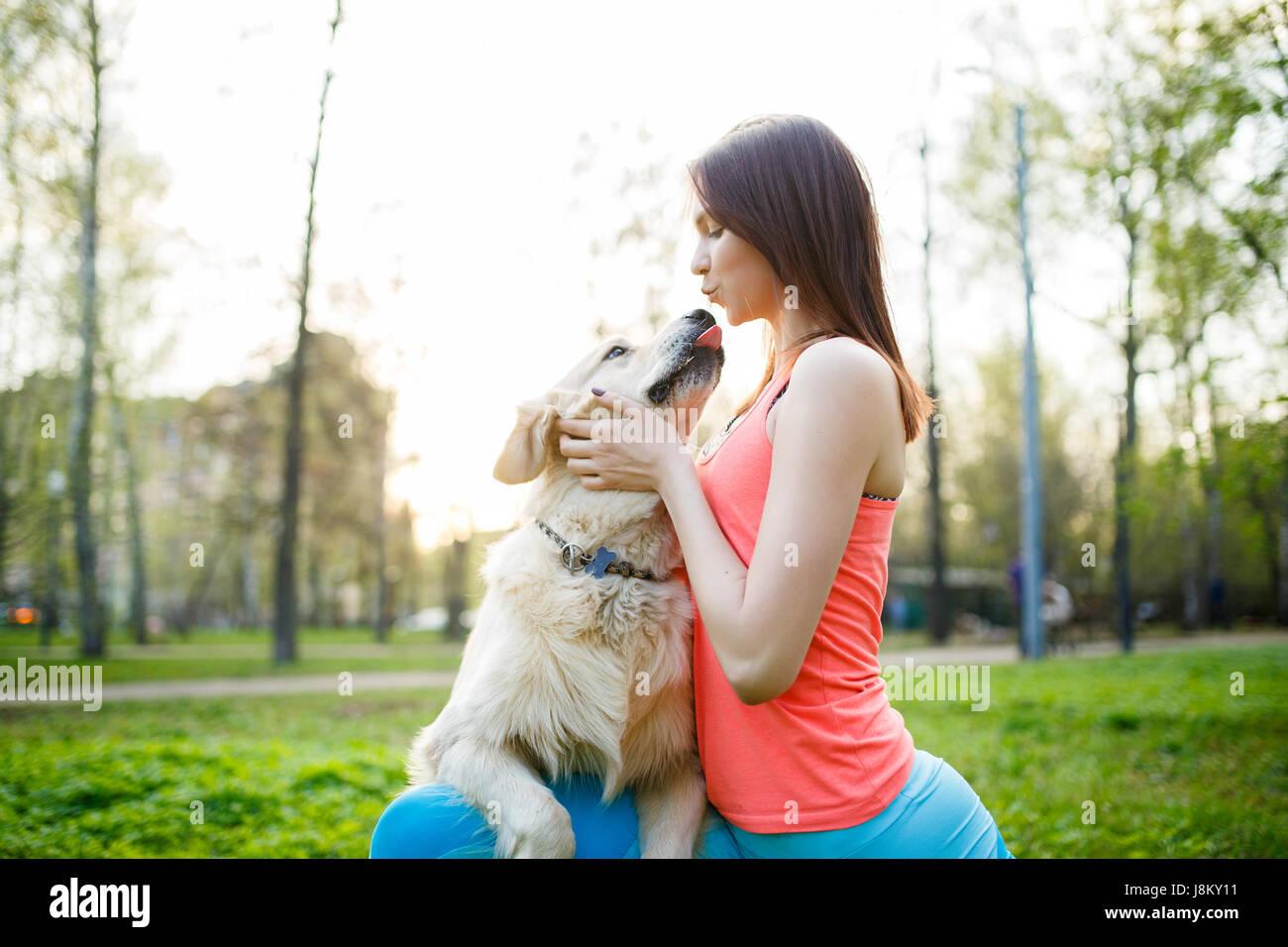 Frau umarmt Hund auf Wiese Stockbild