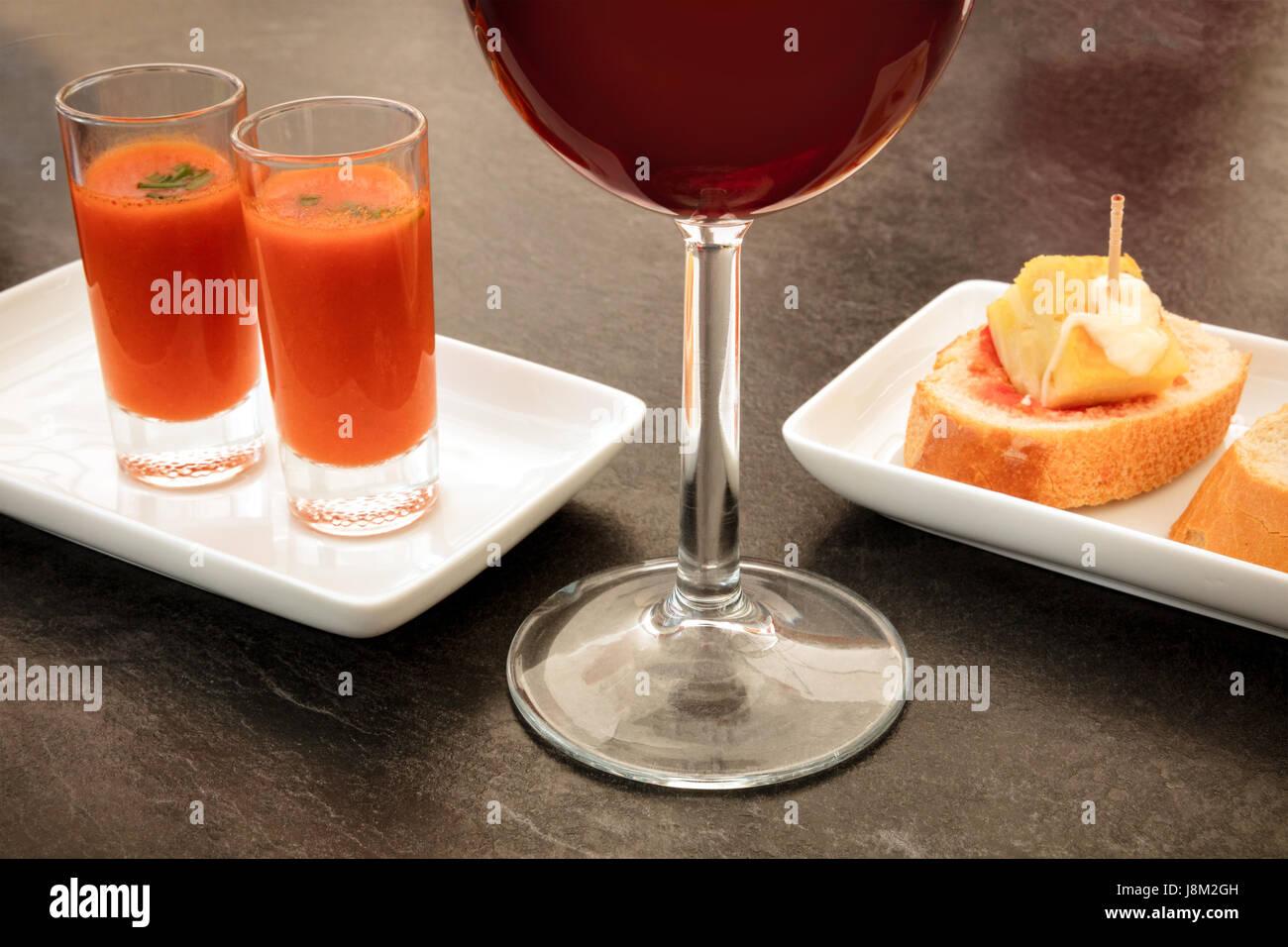 Spanische Tapas in einer modernen Bar. Ein Glas Rotwein, zwei Schüsse von Gazpacho kalte Tomatensuppe und Pinchos Stockbild