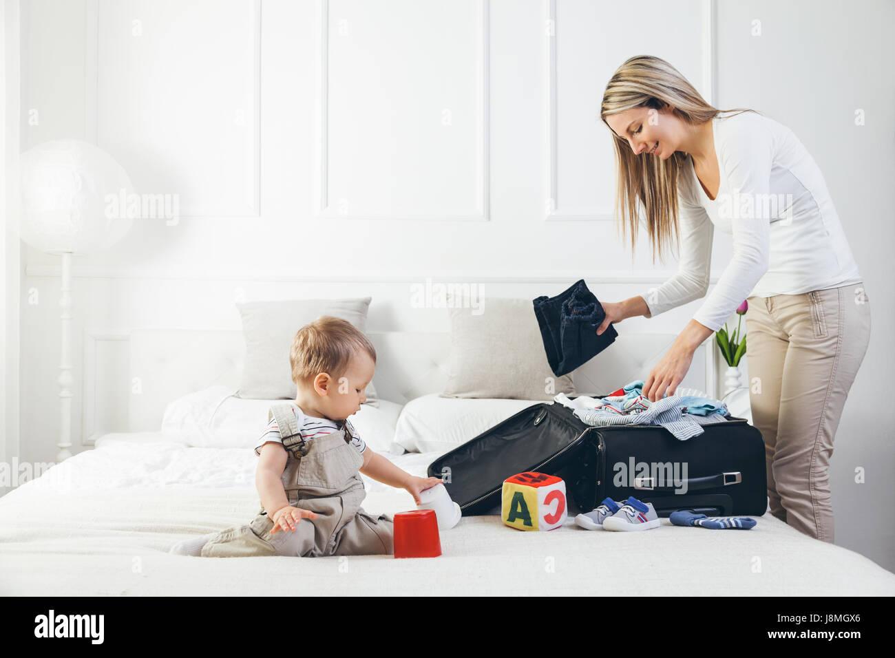 Reisen mit Kindern. Glückliche Mutter mit ihrem Kind Verpackung Kleidung für ihren Urlaub Stockbild
