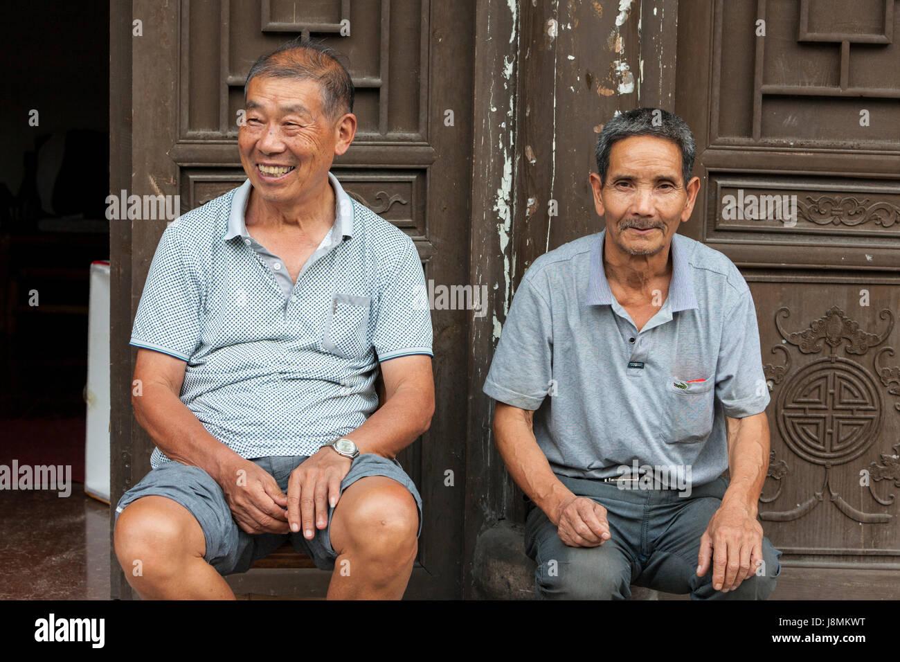 Yantou, Boteli, Zhejiang, China.  Im mittleren Alter Männer sitzen vor ihrer Haustür. Stockbild