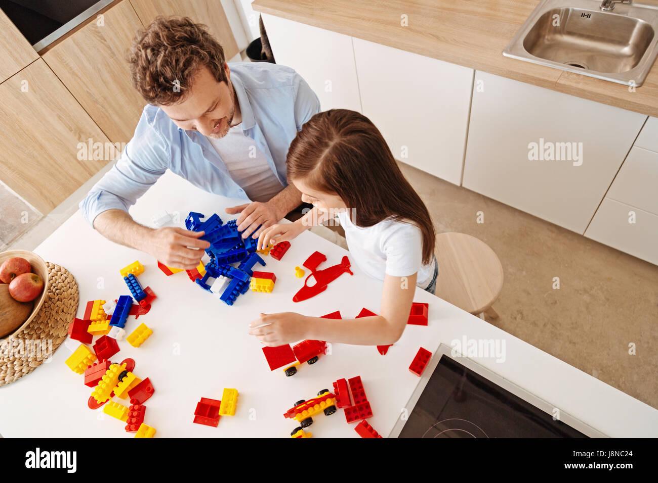 In vollem Gange. Fröhlich lächelnd Vater und seiner kleinen Tochter wird total engagiert zusammen spielen, Stockbild