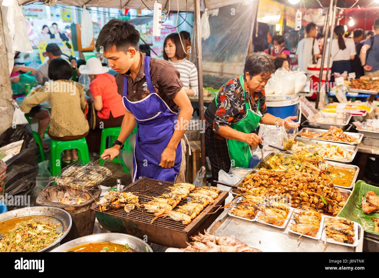 CHIANG MAI, THAILAND - 27 AUGUST: Man kocht Garnelen auf dem Grill am Sonntagsmarkt (Walking Street) am 27. August Stockbild