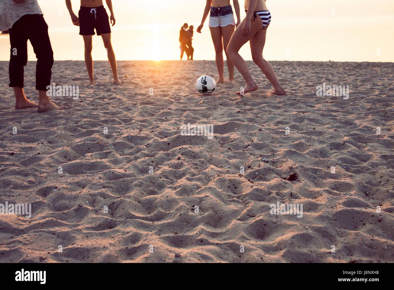 Junge Männer, junge Frau und Teenager-Mädchen (16-17) Fußball spielen auf Sand bei Sonnenuntergang Stockfoto