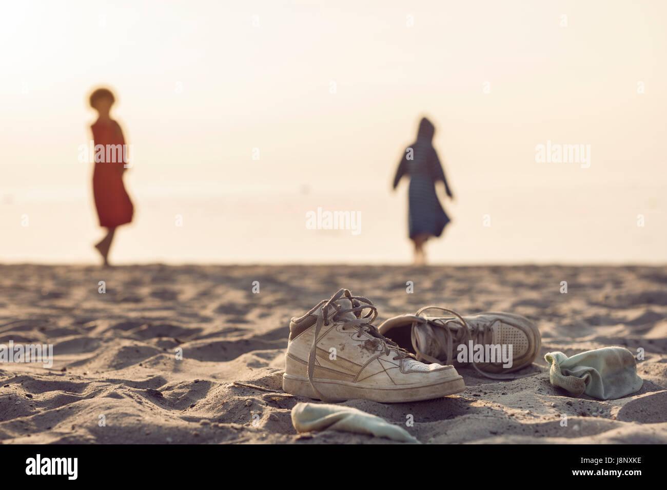 Zwei Frauen am Strand, Schuhe im Vordergrund stehen Stockfoto