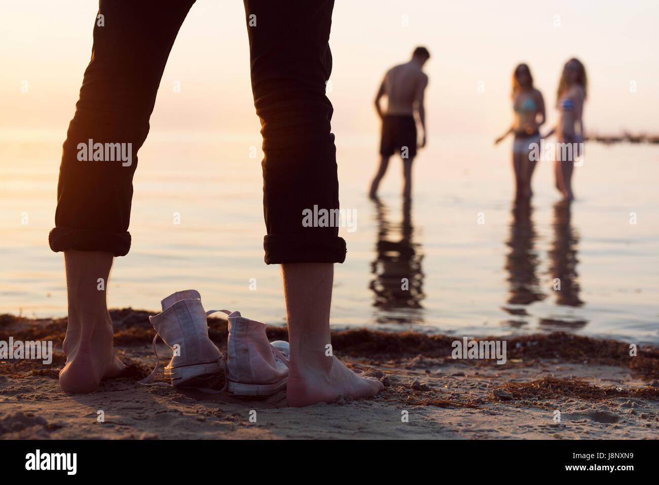Junge Mann stand am Strand während der jungen Frau und Teenager-Mädchen (16-17) und junger Mann waten im Meer bei Sonnenuntergang Stockfoto