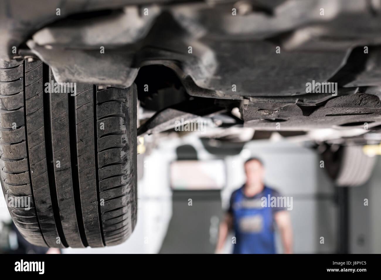 Vordere Auto Suspension. Der garage Mechaniker angehoben, das Auto auf der Hebebühne Stockbild