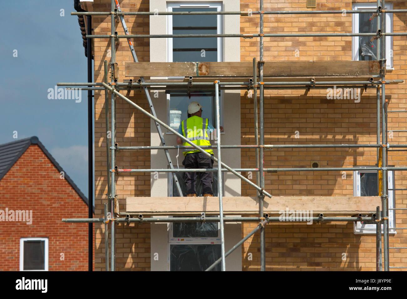 Bauherren, die Arbeit an einer neuen Wohnsiedlung auf Gerüsten Stockbild
