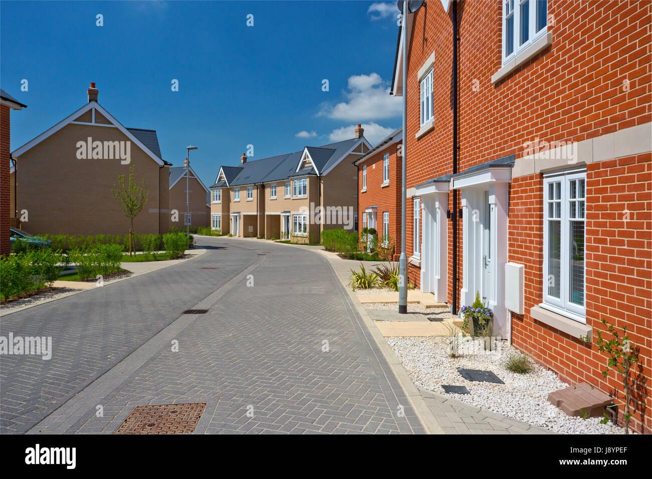 Eine leere Straße in eine meist komplette Neuentwicklung Gehäuse Stockbild