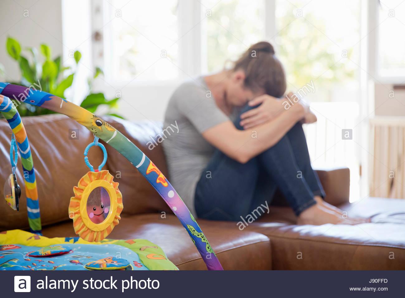 Unglückliche Mutter mit Post-Natal-Depression leiden sitzt auf Sofa Stockbild