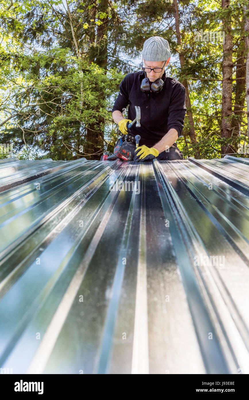Mann arbeitet Installation Metalldach auf Schuppen. Stockbild