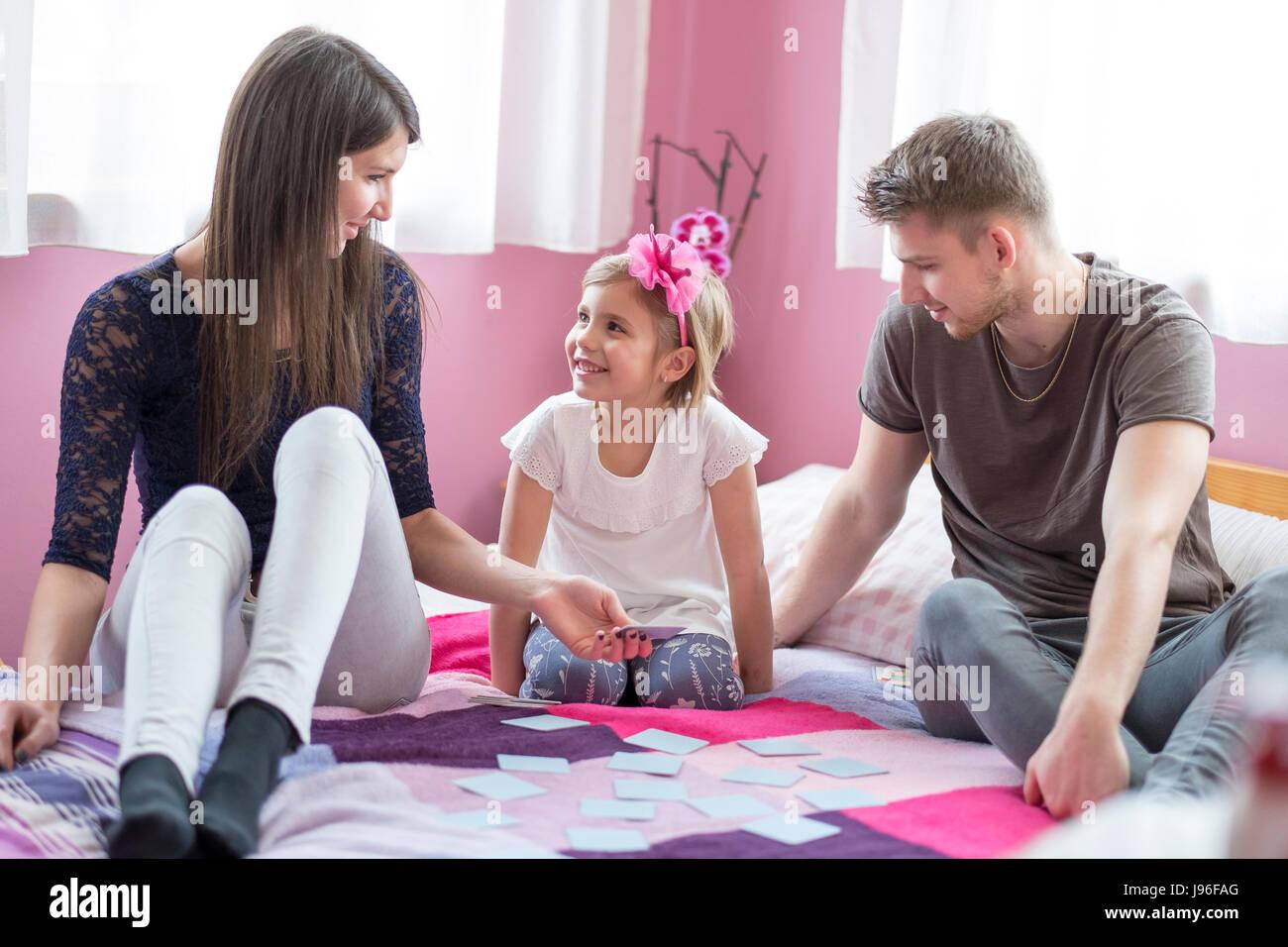 Mutter und Tochter im Bett spielen. Familienspaß Konzept Stockbild
