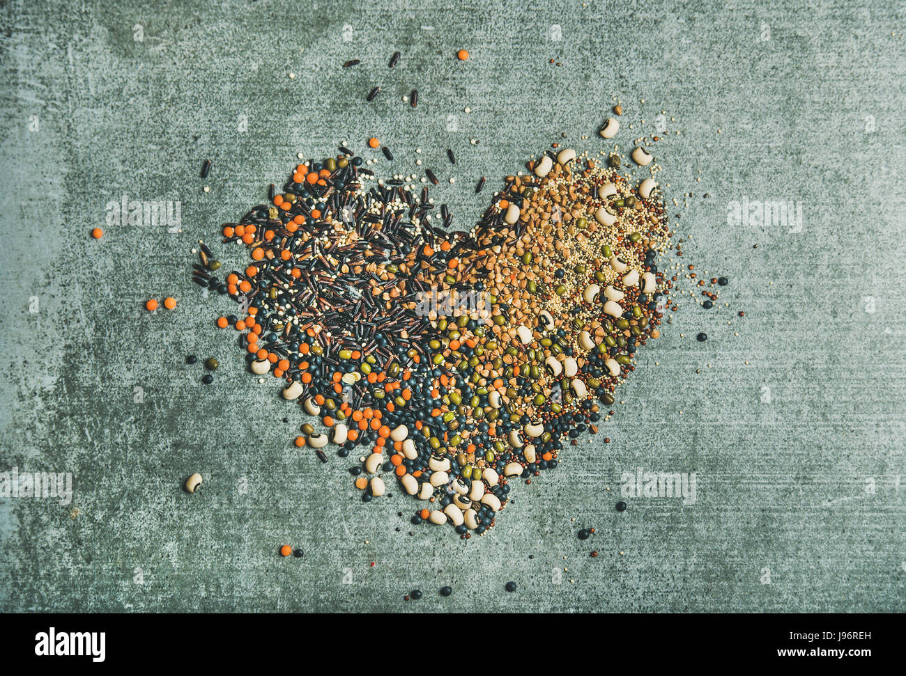 Verschiedene rohe Getreide, Bohnen und Getreide in Form von Herzen Stockbild