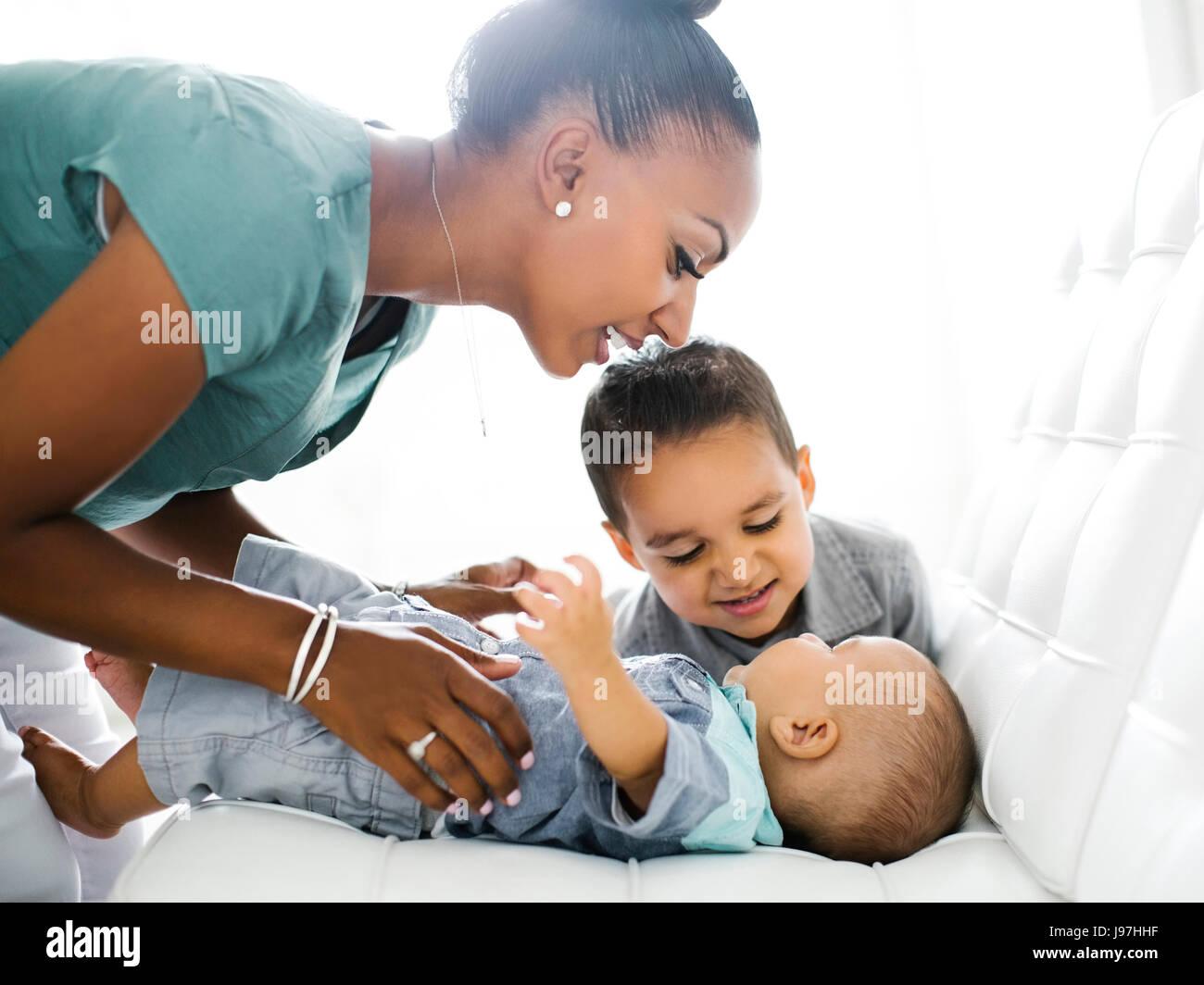 Mutter mit zwei Söhnen (2-5 Monate, 2-3) auf sofa Stockfoto