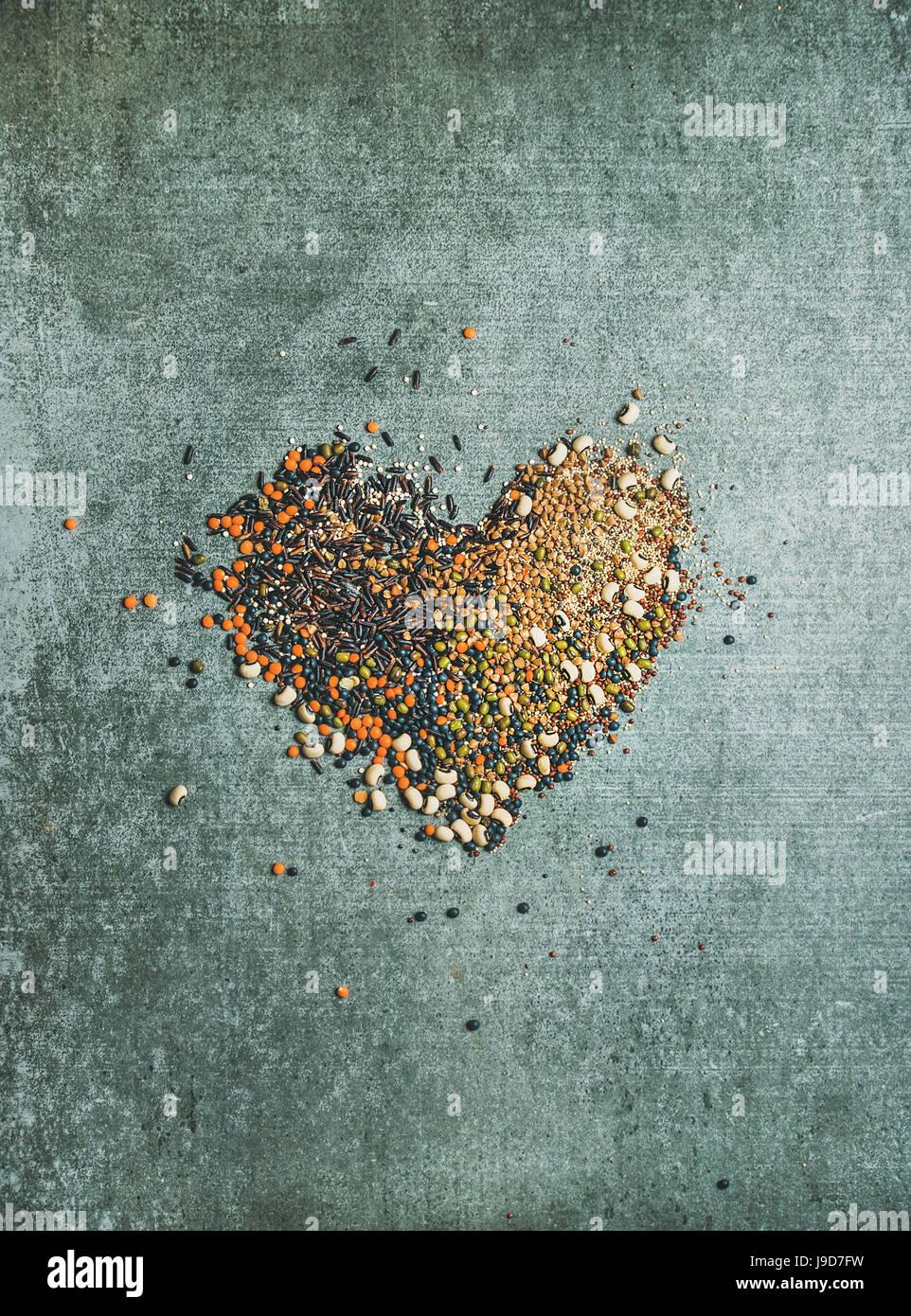 Vielzahl von rohem Getreide, Bohnen, Getreide in Form von Herzen Stockbild