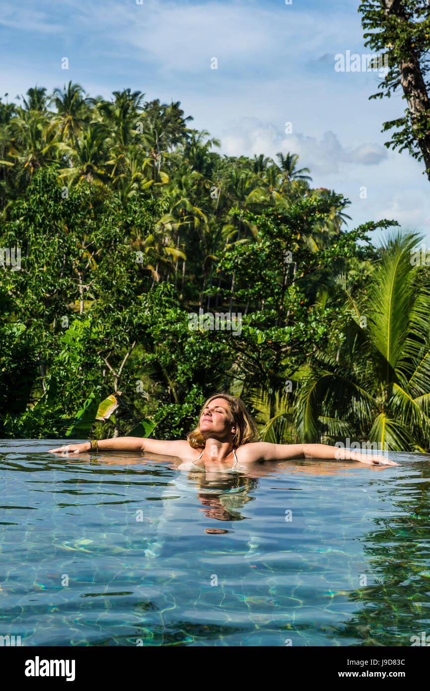 Frau genießen einen überlaufenden Pool über einem Tal im Kamandalu Ubud Resort, Ubud, Bali, Indonesien, Stockbild