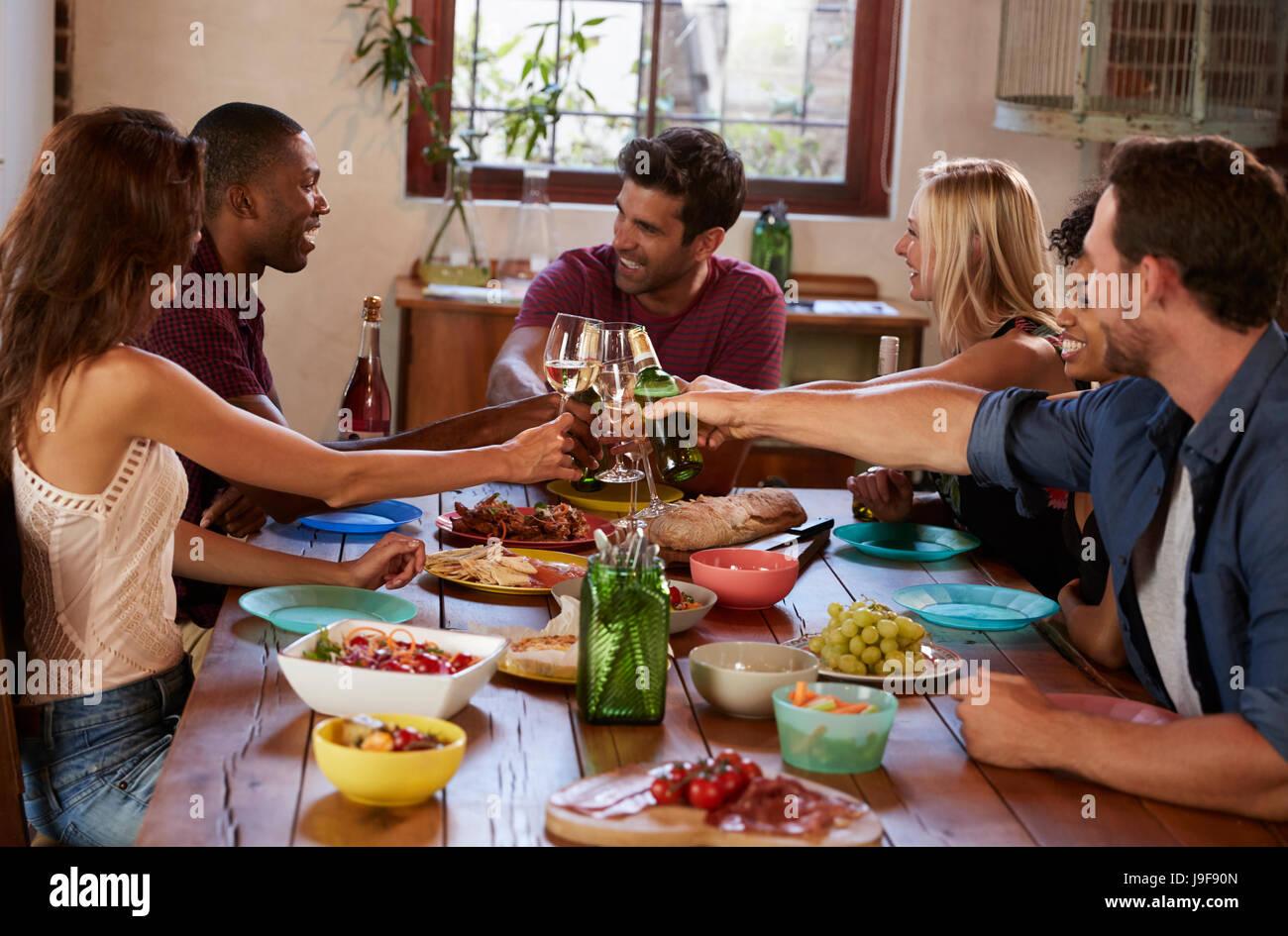 Sechs junge Erwachsene Freunde machen einen Toast auf einer Dinner-party Stockbild