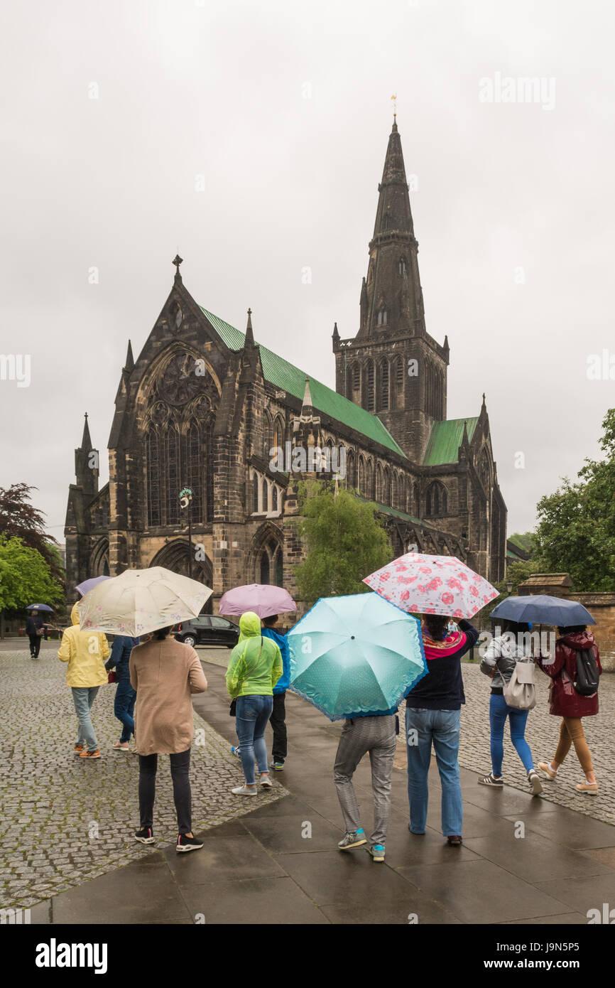 Glasgow Cathedral - asiatische Touristen im Regen, Glasgow, Schottland, Großbritannien Stockbild