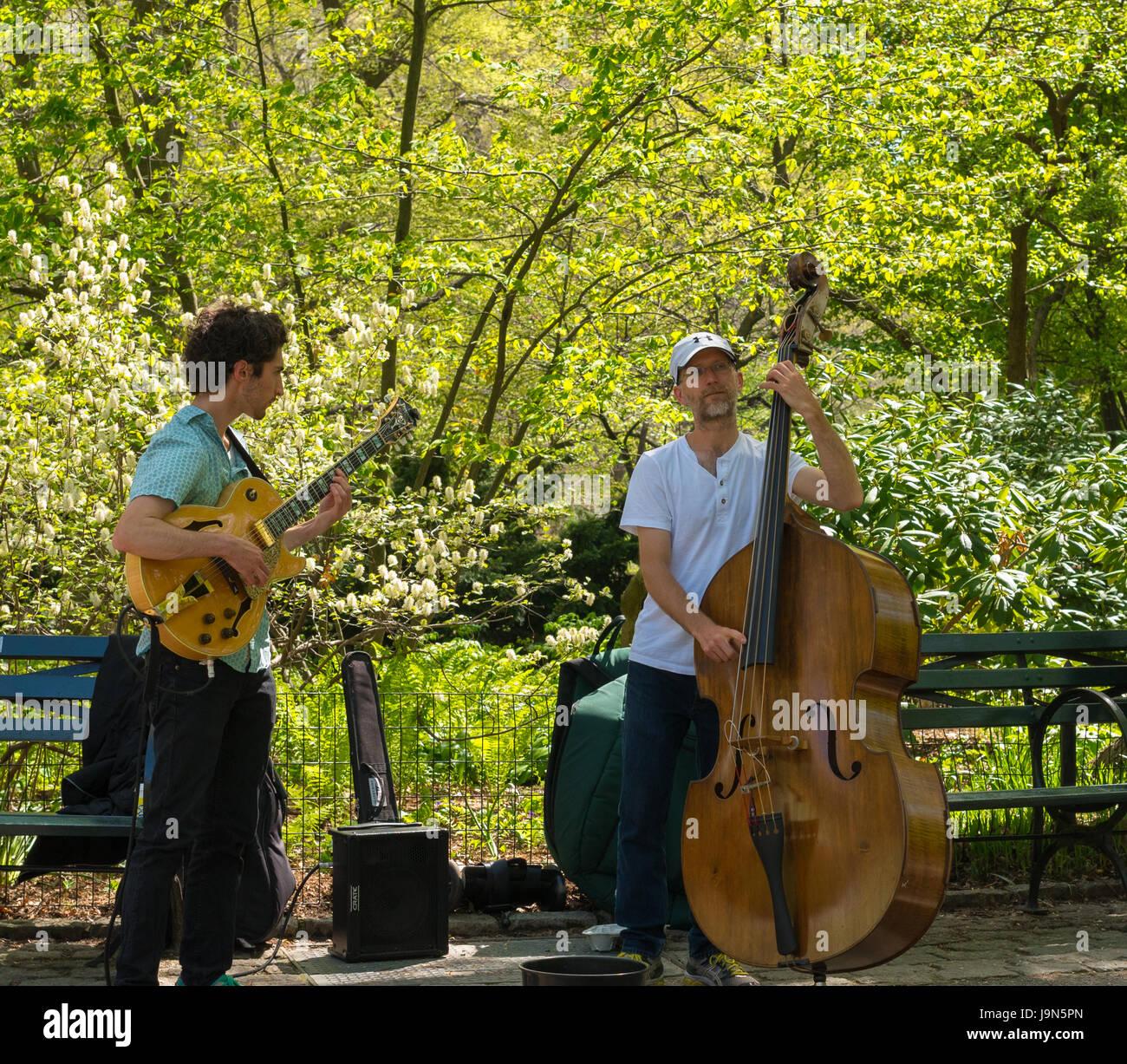 New York, NY USA--28. April 2017--eine e-Gitarre und aufrechte Bassist Durchführung musikalisch im New Yorker Stockbild
