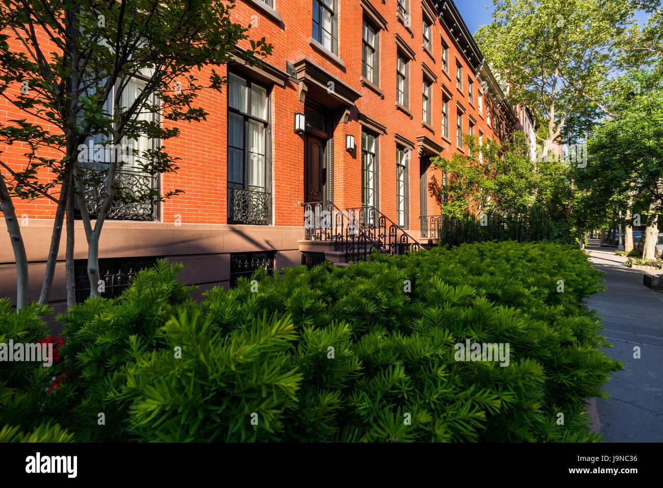 19. Jahrhundert Stadthäuser mit Backsteinfassaden und schmiedeeiserne Geländer. Sommer in Chelsea. Manhattan, Stockbild
