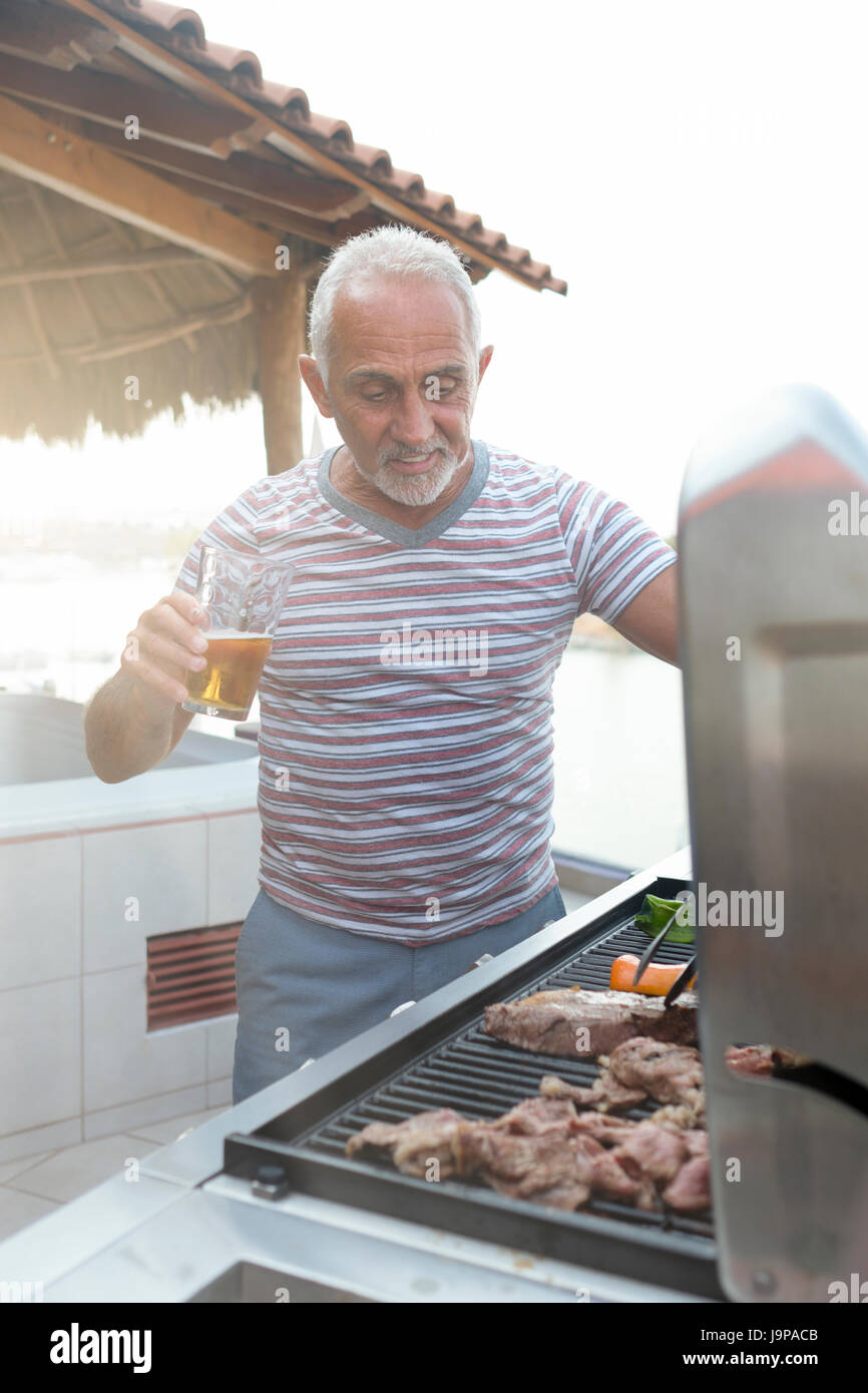 Kaukasischen Mann rund 60 Grillen von Fleisch und Gemüse auf ein Gas-Grill und genießen Sie ein Glas Bier Stockbild