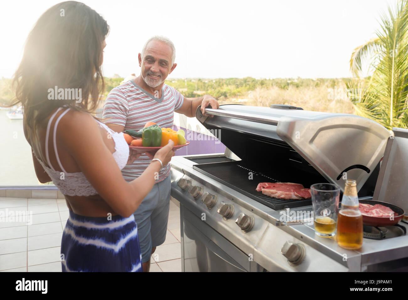 Frau bringt Gemüse mit einem Mann Grillen etwas Fleisch im freien Stockbild