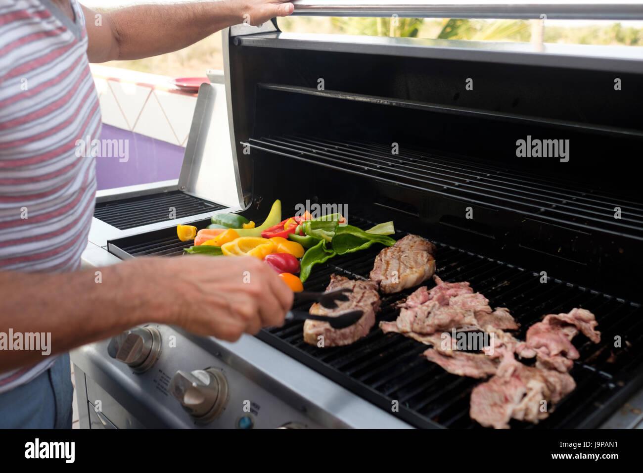 Mann, Grillen Steaks und verschiedene Arten von Paprika auf ein Gas-Grill, Nahaufnahme Stockbild