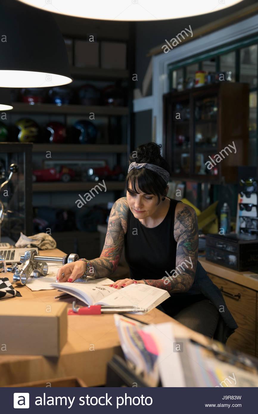 Weibliche Motorrad-Mechaniker betrachten Bauteilkatalog Stockbild