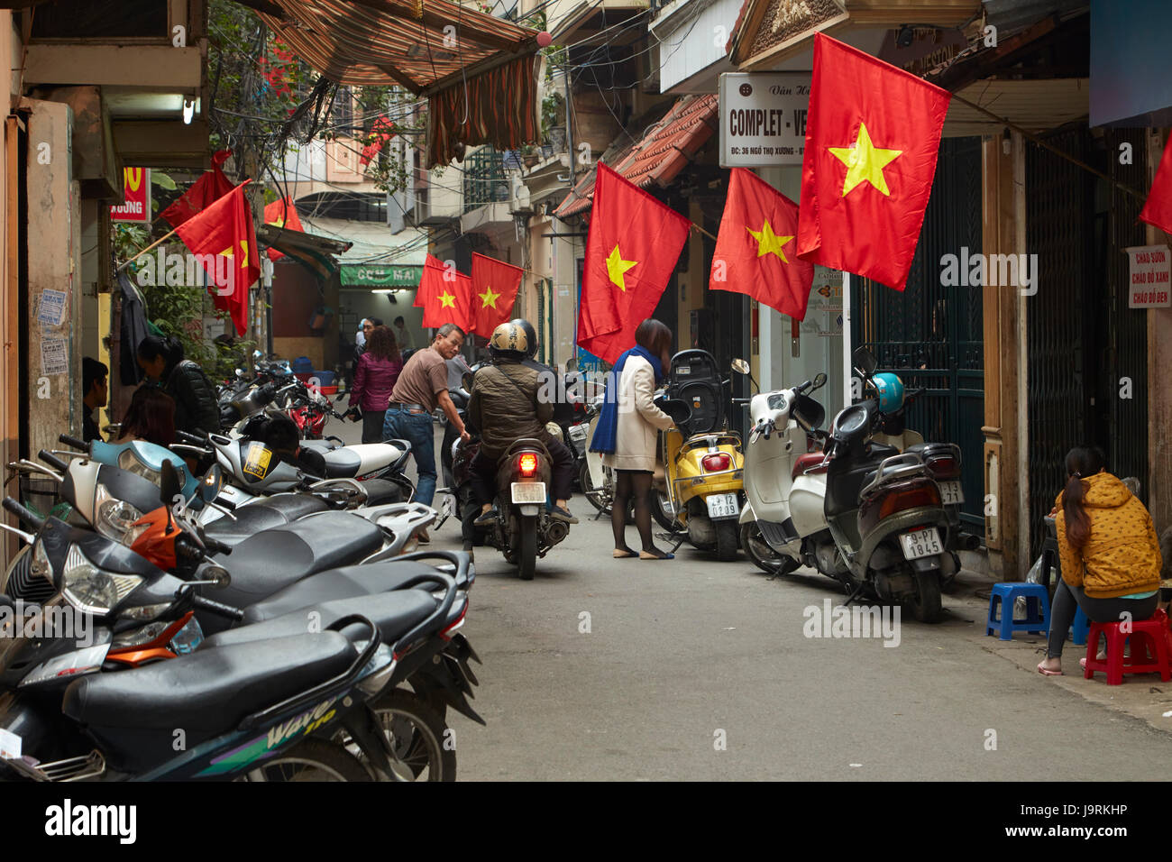 Motorräder in und vietnamesische Flaggen in belebten Altstadt, Hanoi, Vietnam Stockbild