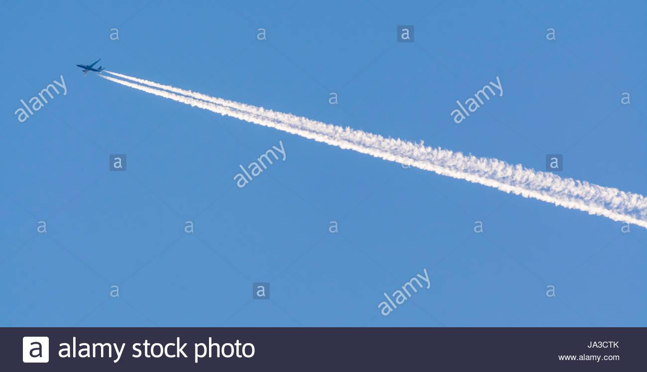 Kondensstreifen von ein Düsenjet fliegt hoch in den Himmel gegen blauen Himmel. Stockbild