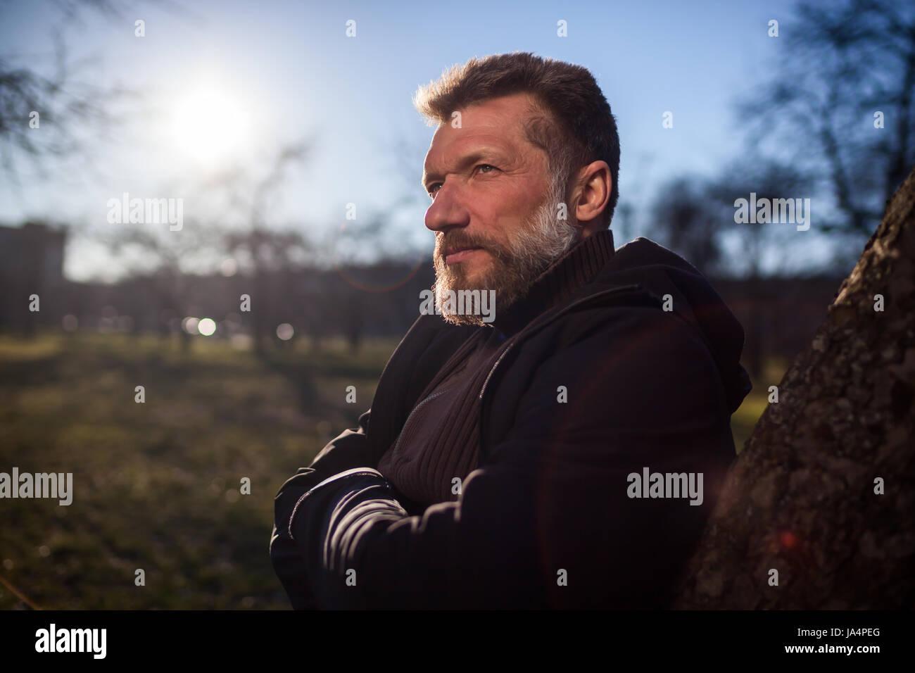 Porträt eines älteren Mannes in einem Park. Er schaut nachdenklich in die Ferne, planen und träumen Stockbild