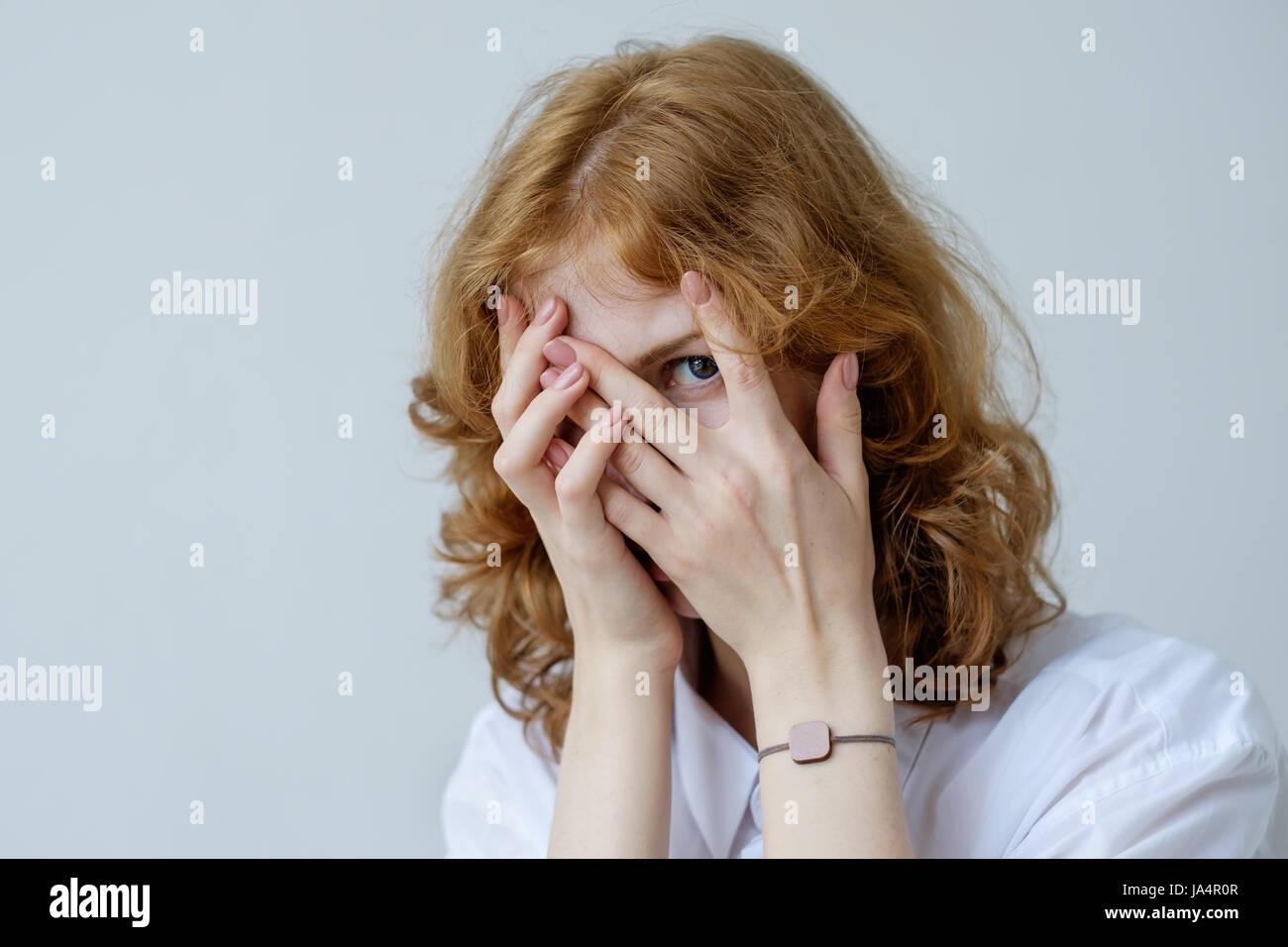 Ein rothaariges Mädchen mit locken in Verlegenheit bedeckt ihr Gesicht mit den Händen und den Fingern Stockbild
