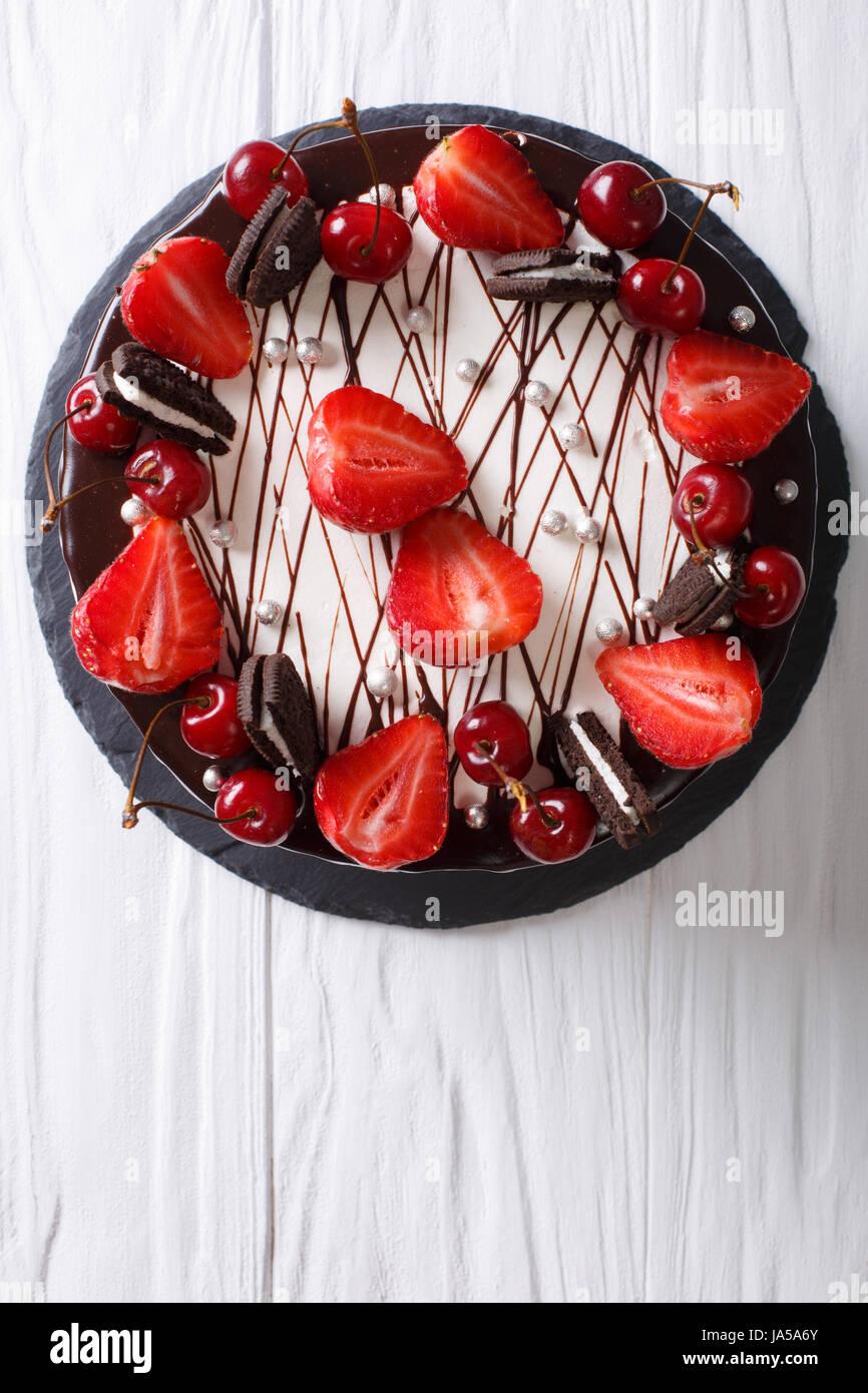 festliche Schokoladentorte mit Erdbeere und Kirsche Nahaufnahme auf dem Tisch. vertikale Ansicht von oben Stockbild