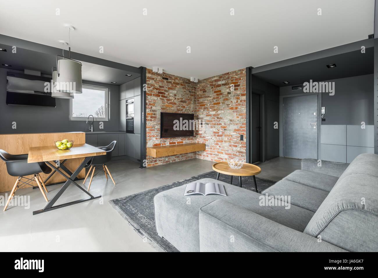 Graue und weiße Wohnung im industriellen Stil mit offener Wohn- und ...