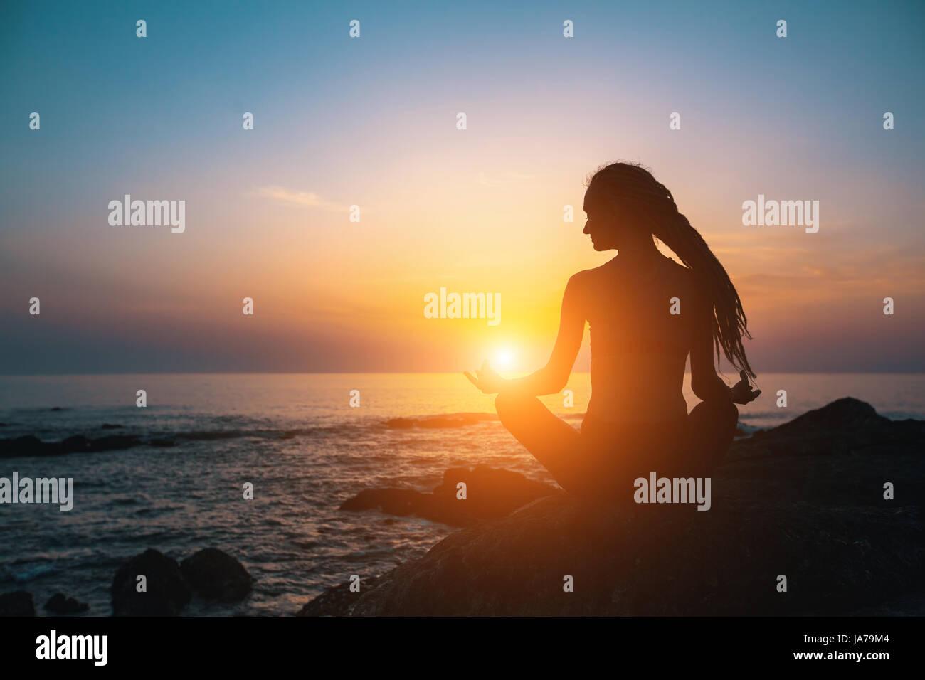 Meditation-Mädchen am Meer während des Sonnenuntergangs. Yoga-Silhouette. Fitness und gesunde Lebensweise. Stockfoto