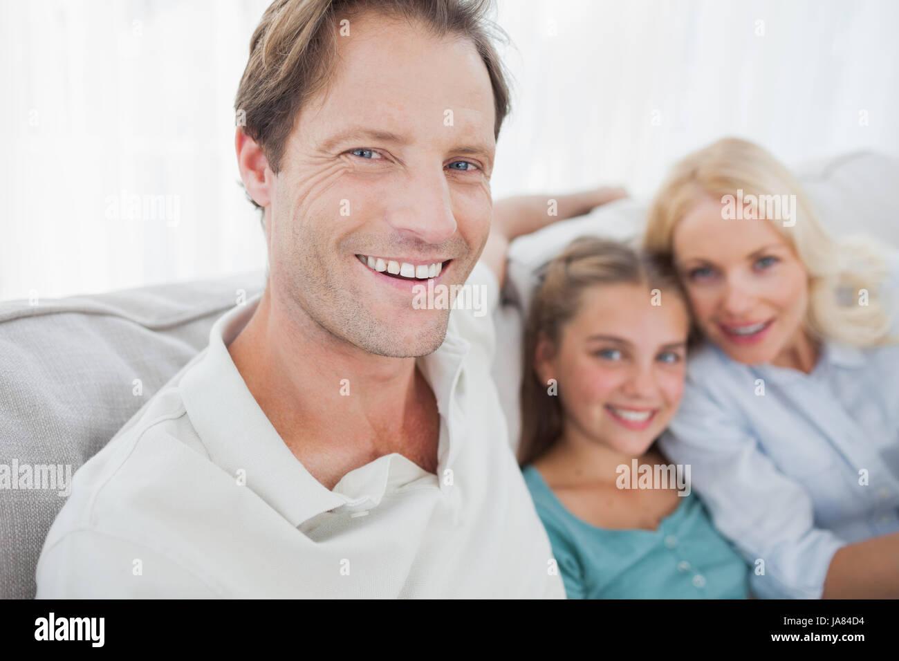Porträt eines Vaters mit Familie hinter sitzen auf einer couch Stockfoto