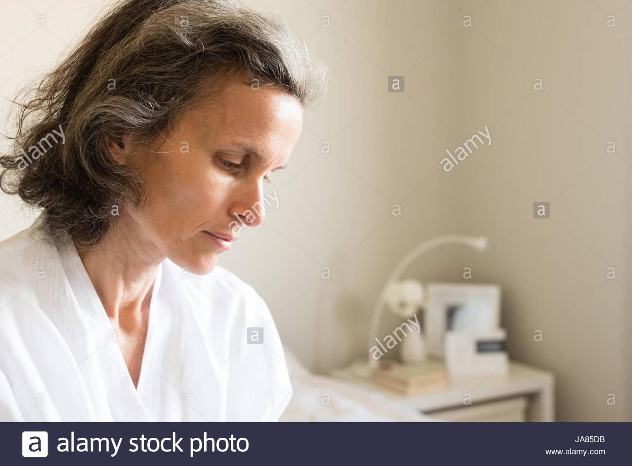 Höhenplan der mittlere gealterte Frau mit grauen Haaren sitzen auf Bett in weißem Gewand (Tiefenschärfe) Stockbild
