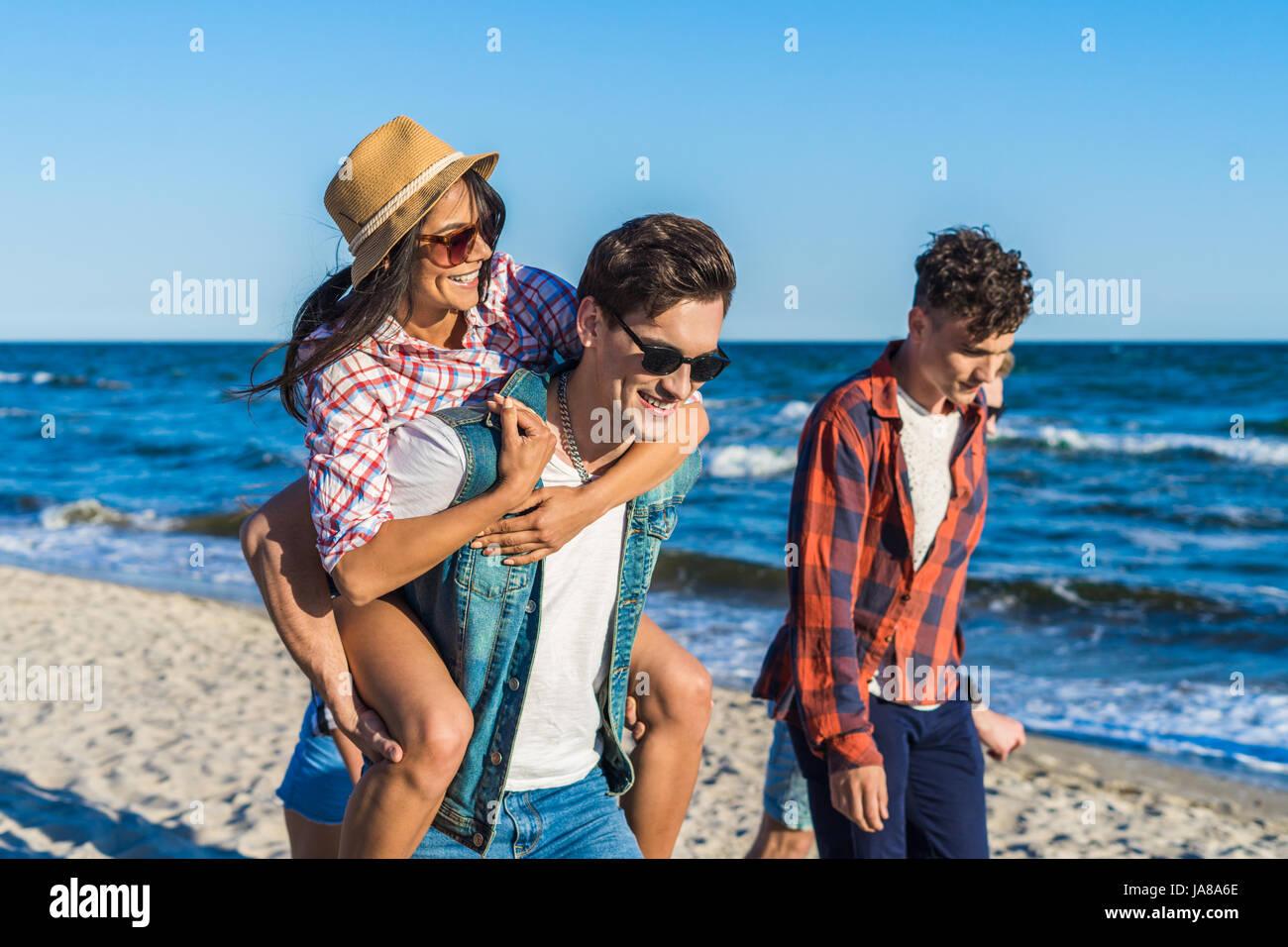 junge lustige paar Sonnenbrillen Huckepack auf den Strand. Stockbild