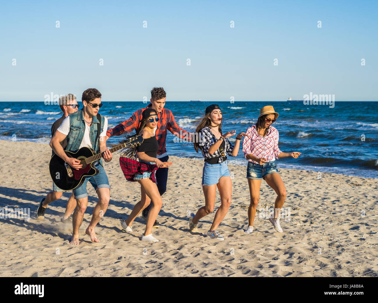 Party am Strand mit Gitarre. Freunde, die zusammen tanzen am Strand Stockbild