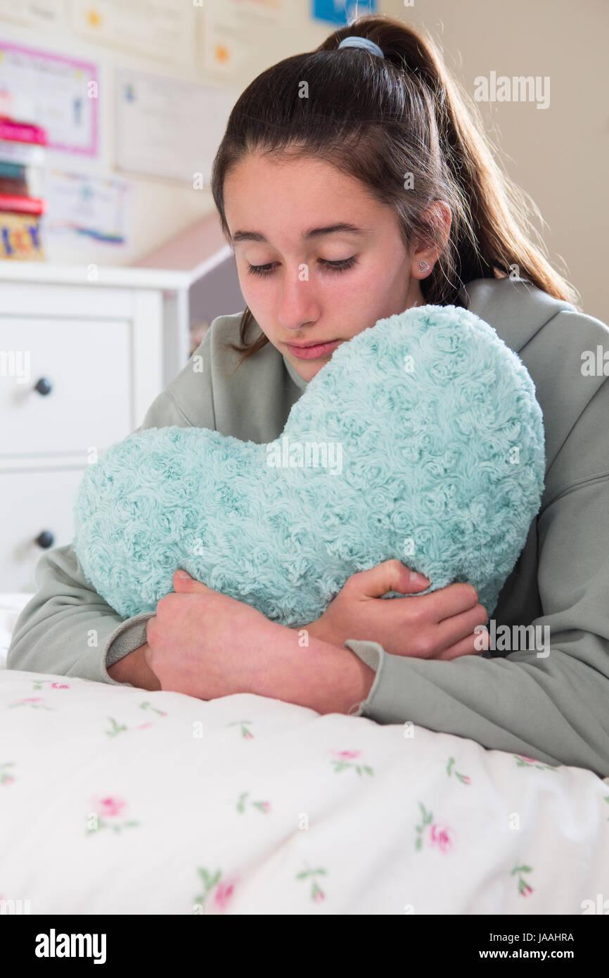 Junges Mädchen auf Bett umarmt Herz geformten Kissen liegend Stockbild